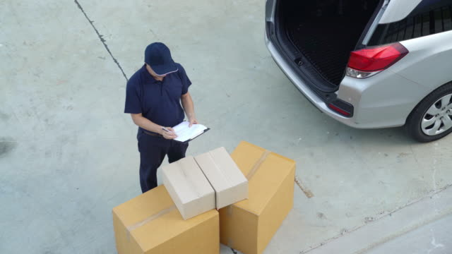 delivery concept,delivery man smiling holding a cardboard box. - delivery person stock videos & royalty-free footage