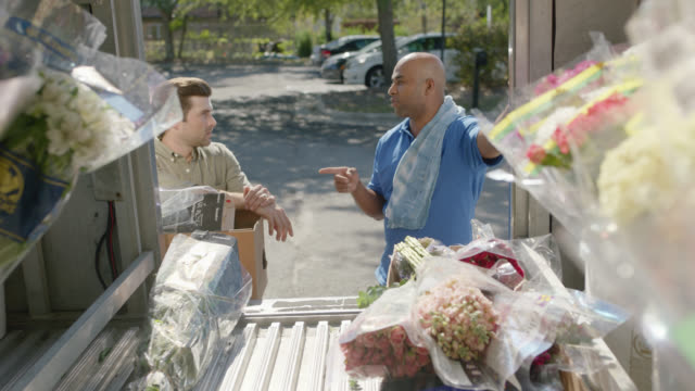 delivery driver discusses flower options with flower shop owner before unloading - unloading stock videos & royalty-free footage