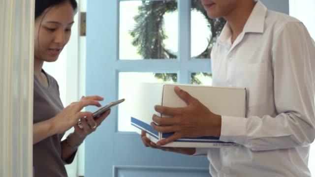 顧客の署名を取るためにスマートフォンを使用して配信ドライバ - 段ボール箱点の映像素材/bロール