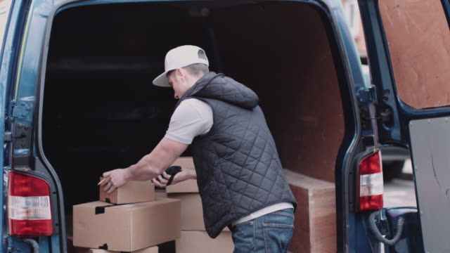 vídeos de stock, filmes e b-roll de delivery man at van scanning boxes with barcode scanner - entregador