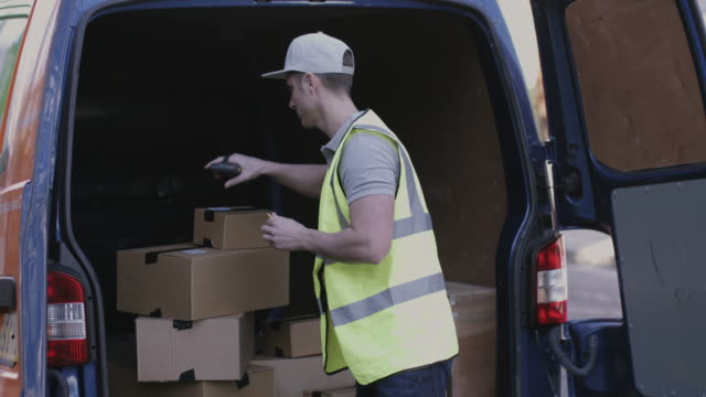 vidéos et rushes de delivery man at van scanning boxes with barcode scanner - facteur