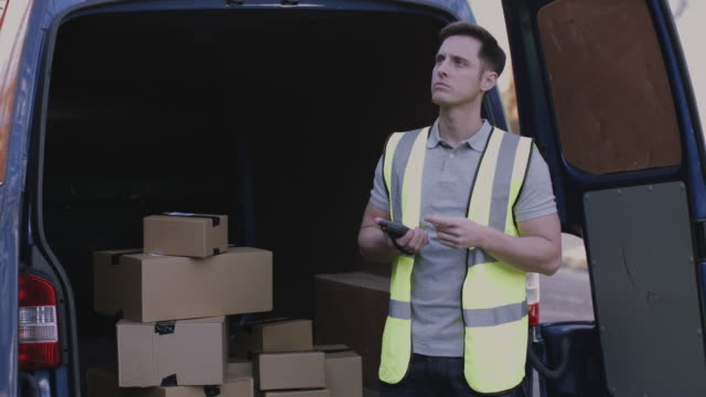 Delivery man at van scanning boxes with barcode scanner