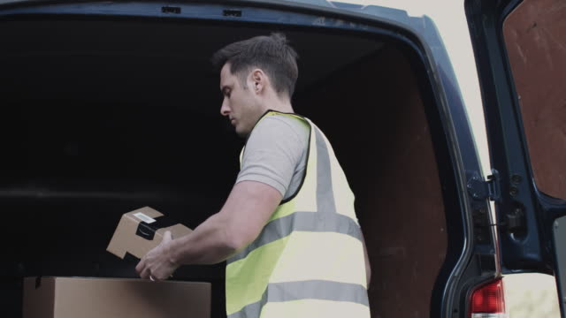 delivery man at van scanning boxes with barcode scanner - delivery person stock videos & royalty-free footage