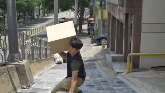 delivery man carrying delivery boxes uphill - uphill stock videos & royalty-free footage