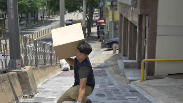 vidéos et rushes de delivery man carrying delivery boxes uphill - qui monte