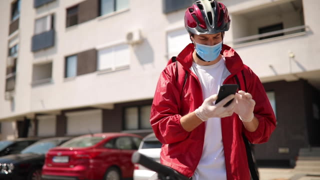 delivery man checking directions on smartphone - helmet stock videos & royalty-free footage