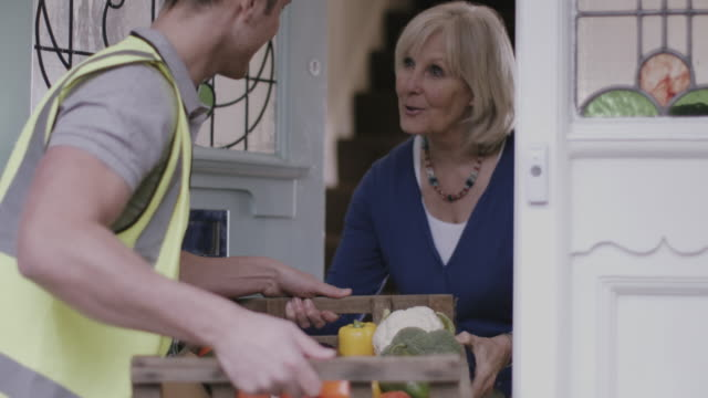 vidéos et rushes de delivery man delivering fruit and vegetables at home - embrasure de porte