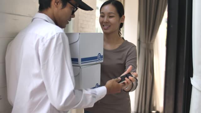 スマート フォンと署名の家にパッケージを提供する配達人 - 配達点の映像素材/bロール