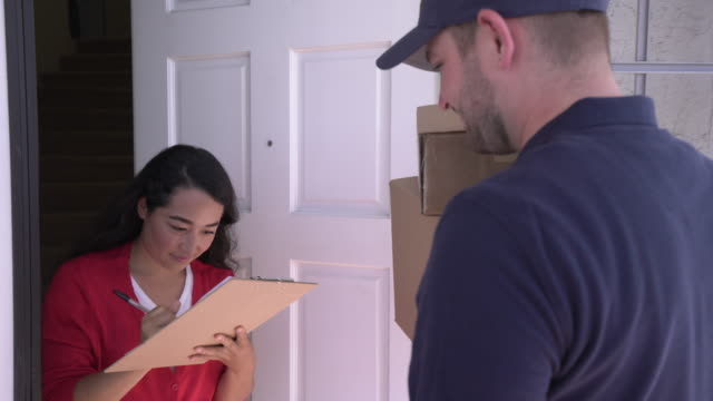 ms delivery man delivering packages to a woman at home - receiving stock videos & royalty-free footage