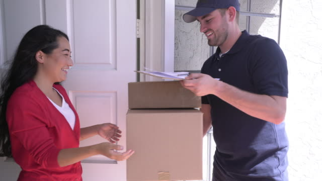 ms delivery man delivering packages to a young woman - bekommen stock-videos und b-roll-filmmaterial