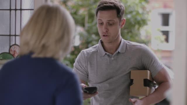 vídeos y material grabado en eventos de stock de delivery man delivering parcel at home - mujeres mayores