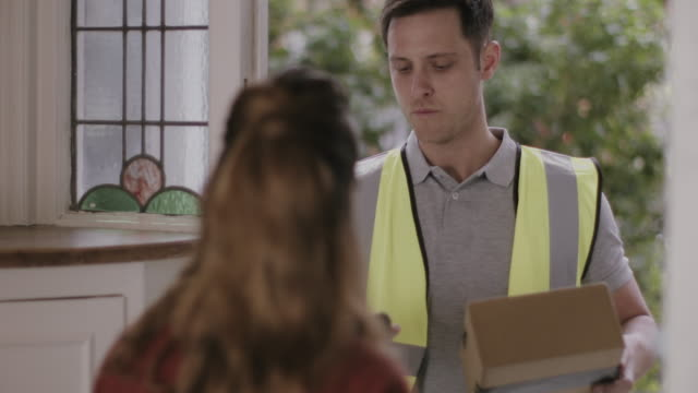 delivery man delivering parcel at home - receiving stock videos & royalty-free footage