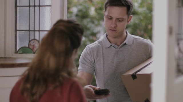 delivery man delivering parcel at home - receiving stock videos and b-roll footage