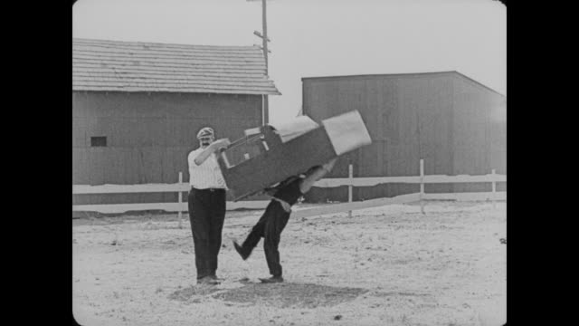 1920 a delivery man drops a piano on man (buster keaton) and makes man sign for the delivery before removing the piano from on top of him - portare video stock e b–roll