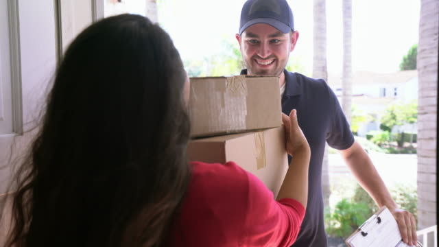 ms delivery man giving packages to a woman at the door. - receiving stock videos & royalty-free footage
