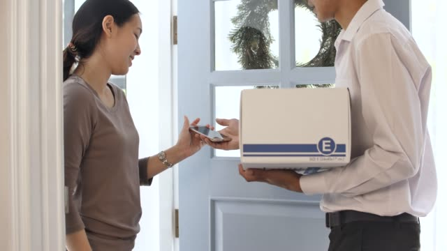 delivery man hands over parcel after recipient signs electronic at home - receiving stock videos and b-roll footage