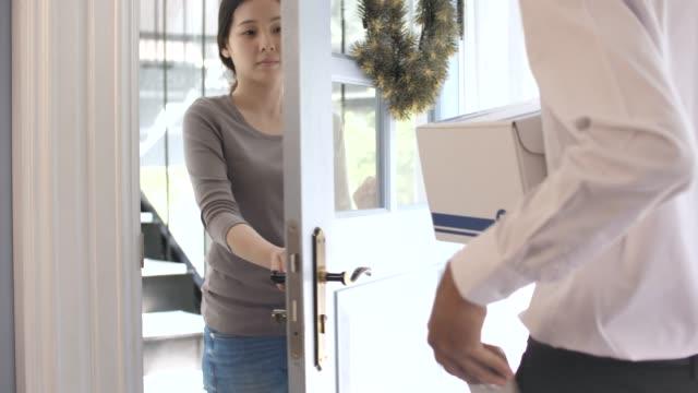 vídeos y material grabado en eventos de stock de entrega hombre manos sobre parcela después de signos de destinatario firma electrónica en el teléfono inteligente - haz de luz