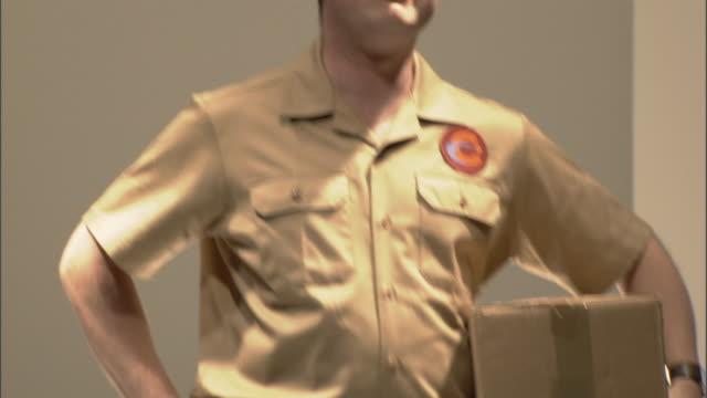 ms tu delivery man holding cardboard box on catwalk and saying thank you / london, england, uk - この撮影のクリップをもっと見る 1064点の映像素材/bロール