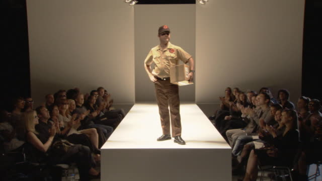 cu zo ws delivery man holding cardboard box on catwalk while audience applauds / london, england, uk - out of context stock videos & royalty-free footage