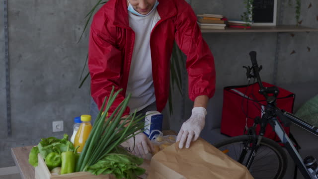 delivery man packing food for delivery during covid-19 pandemic - charitable donation stock videos & royalty-free footage