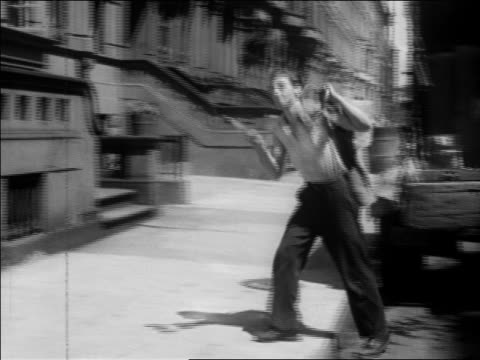 B/W 1938 delivery man playing paddleball as he walks towards brownstone / newsreel