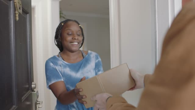 stockvideo's en b-roll-footage met delivery man raps on door knocker and african american woman opens door to receive package. - bron
