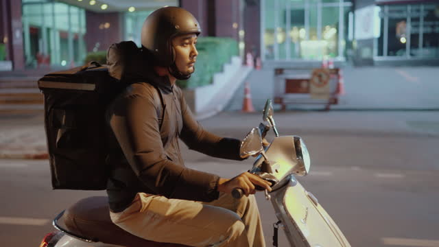 delivery man riding a motorcycle in the city at night - motorbike stock videos & royalty-free footage