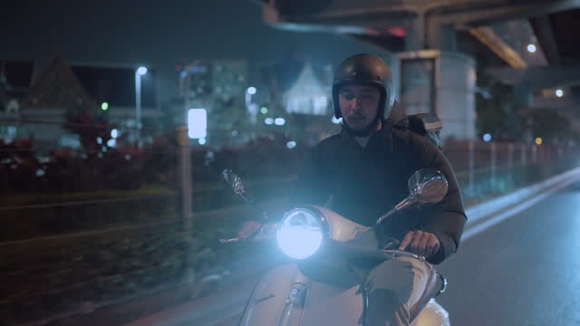 delivery man riding a motorcycle in the city at night - scooter stock videos & royalty-free footage