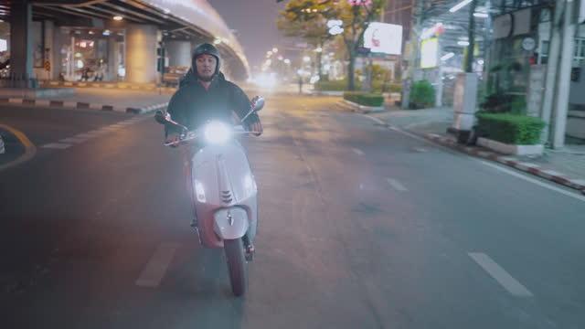 liefermann fährt nachts motorradfahrend in der stadt - motorroller stock-videos und b-roll-filmmaterial