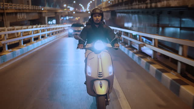 delivery man riding a motorcycle in the city at night - crash helmet stock videos & royalty-free footage