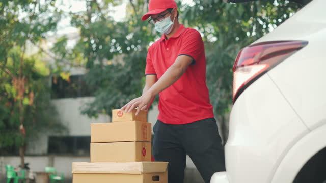 il fattorino prende le scatole dal suo furgone per la consegna - scaricare video stock e b–roll