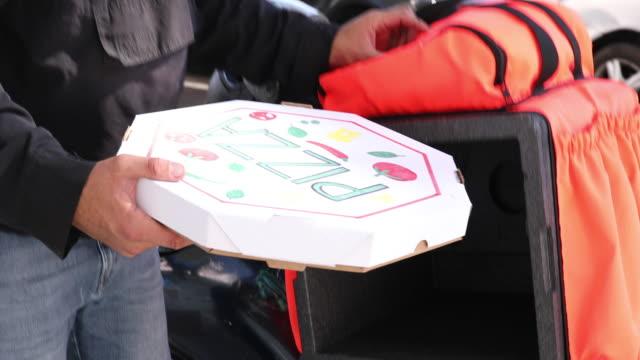 liefermann, der die pizza aus dem rucksack nimmt - motoboy - tragetasche oder tragebeutel stock-videos und b-roll-filmmaterial