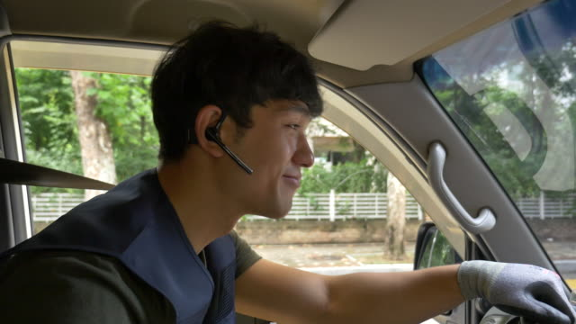 vidéos et rushes de delivery man talking on the phone while driving - profil