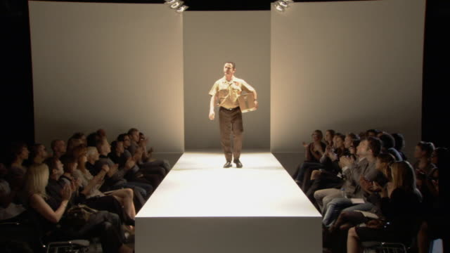 WS Delivery man walking on catwalk with cardboard box while audience applauds / London, England, UK