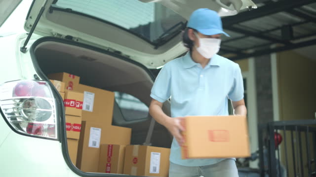 delivery man wearing mask unloading the parcel from his car - unloading stock videos & royalty-free footage