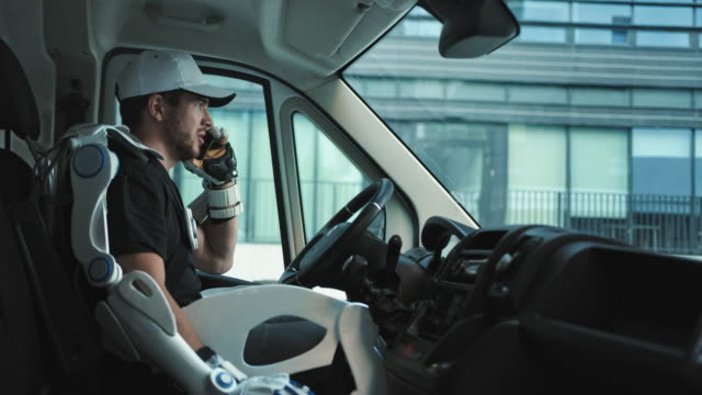delivery man wearing powered exoskeleton in his van. making call - manual worker stock videos & royalty-free footage