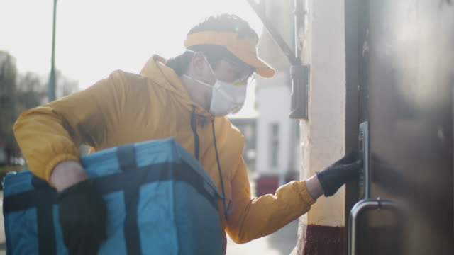 delivery man wearing protective mask and rubber gloves checking address in his smartphone - catering occupation stock videos & royalty-free footage
