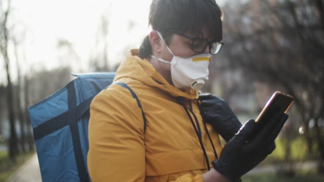 vídeos de stock e filmes b-roll de delivery man wearing protective mask and rubber gloves checking address in his smartphone - aplicação móvel