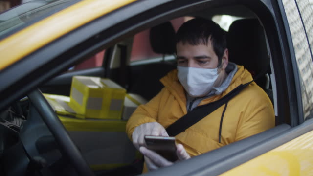delivery man wearing protective mask and rubber gloves checking address in his smartphone - glove stock videos & royalty-free footage