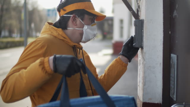 delivery man wearing protective mask and rubber gloves ringing a door - delivering stock videos & royalty-free footage