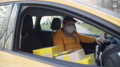 vídeos y material grabado en eventos de stock de el repartidor que lleva máscara protectora y guantes de goma con paquetes de aparcamiento de coche durante una epidemia de enfermedad - correspondencia