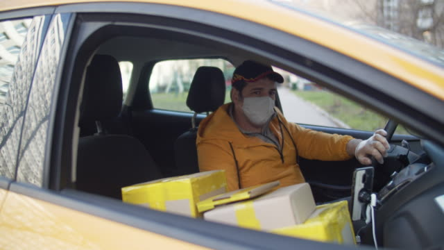 delivery man wearing protective mask and rubber gloves with parcels parking car during an illness epidemic - post office stock videos & royalty-free footage