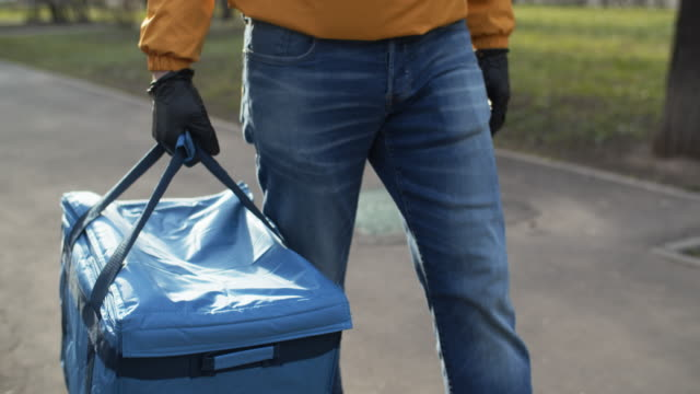 vídeos de stock e filmes b-roll de delivery man wearing protective rubber gloves during an illness epidemic - serviços essenciais