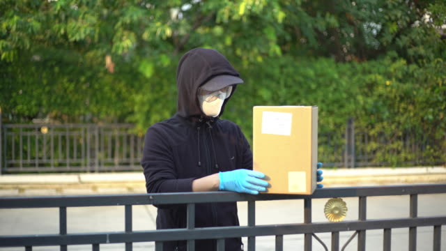 vídeos de stock e filmes b-roll de delivery man wearing safety glasses and face mask putting down the package on the fence and keep distance reduce germ spread - vírus