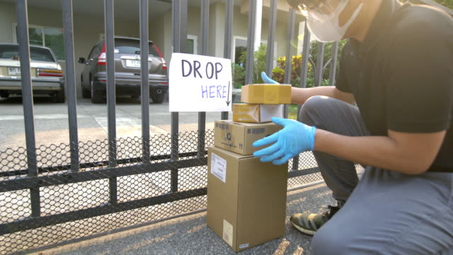 delivery man wearing safety glasses and face mask putting down the package outside the fence for keeping distance reduce germ spread - gesturing stock videos & royalty-free footage