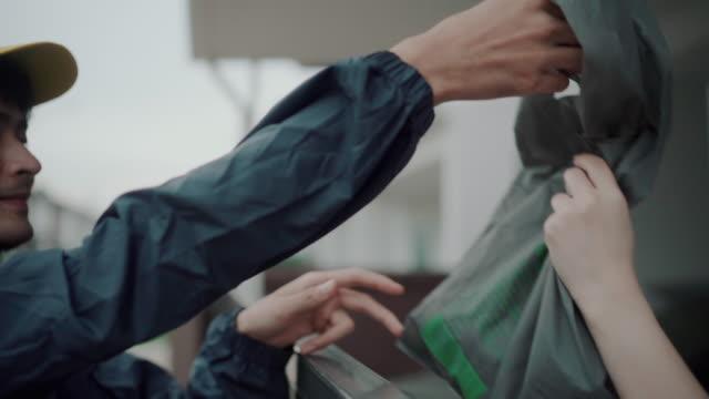 vídeos de stock, filmes e b-roll de entregador com mochila com entrega de comida - receber