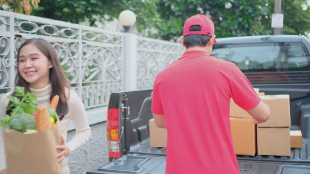 delivery man with red shirt and cap uniform bring grocery bag with vegetable to pretty woman and stay on back of pick-up truck in front of house - 運ぶ点の映像素材/bロール