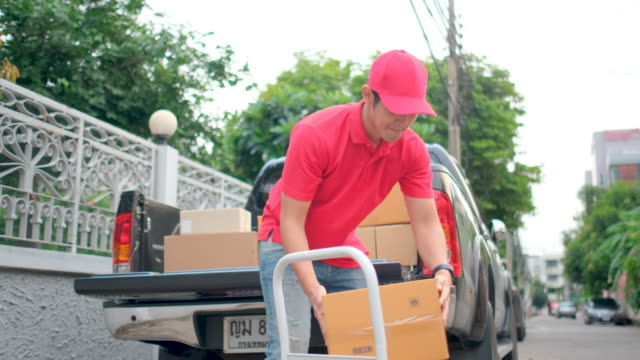 delivery man with red shirt and cap uniform bring some package box our from back of pick-up truck to small hand truck in front of house - 配達員点の映像素材/bロール