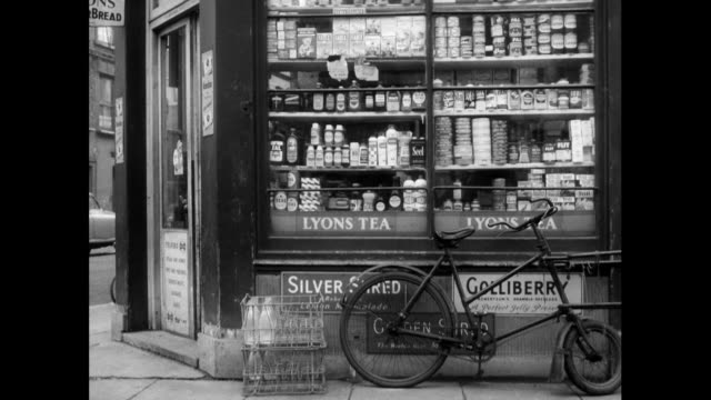 vídeos y material grabado en eventos de stock de delivery men outside small corner shop in the uk; 1963 - bicicleta antigua