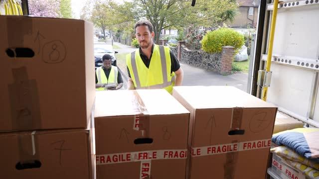 vidéos et rushes de delivery men unloading boxes from van - décharger